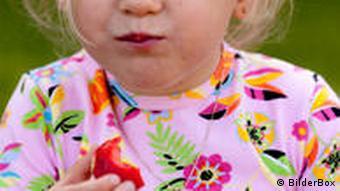 Ein Mädchen verzieht beim Essen einer sauren Erdbeere das Gesicht