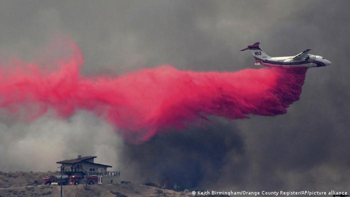 Los bomberos trabajan para proteger una casa mientras un camión cisterna sobrevuela una colina durante el incendio Bobcat en Juniper Hills, California. (19.09.2020)