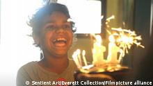 A little boy with a broad grin watches sparkly cake candles burn (Sentient Art/Everett Collection/Filmpicture alliance)