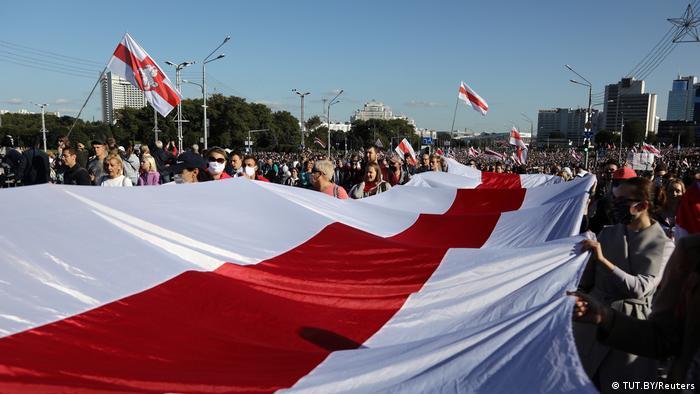 Pessoas segurando bandeira gigantesca branca com listra vermelha