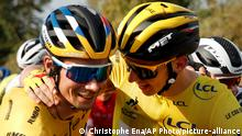 Slovenia's Primoz Roglic, left, who lost his overall leader's yellow jersey to Slovenia's Tadej Pogacar, right, gets a hug during the twenty-first and last stage of the Tour de France cycling race over 122 kilometers (75.8 miles), from Mantes-La-Jolie to Paris, France, Sunday, Sept. 20, 2020. (AP Photo/Christophe Ena)