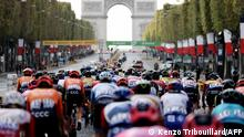 The pack rides on the Champs Elysees avenue with the Arc de Triomphe in the background during the 21st and last stage of the 107th edition of the Tour de France cycling race, 122 km between Mantes-la-Jolie and Champs Elysees Paris, on September 20, 2020. (Photo by KENZO TRIBOUILLARD / AFP)