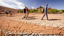 Trekkers follow a dried out river bed in Morocco