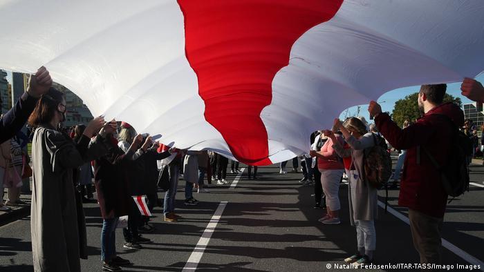 Протестующие держат в руках огромный бело-красно-белый флаг