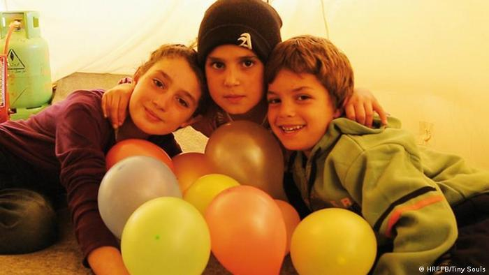 Human Rights Film Festival 2020: image from the film Tiny Souls. Three children holding their heads together in a tent and smiling into the camera. They have balloons in front of them (HRFFB/Tiny Souls)