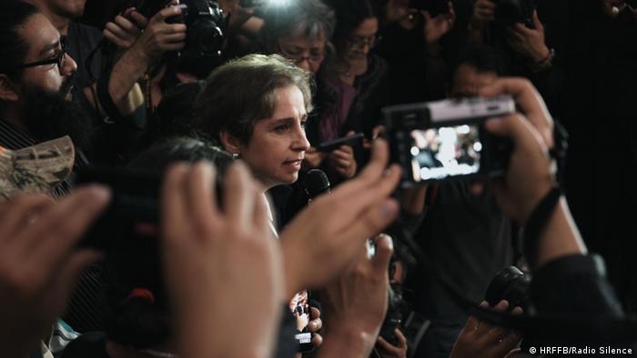 Human Rights Film Festival 2020: image from the film Radio Silence. A woman is speaking into a microphone, surrounded by cameras (HRFFB/Radio Silence)