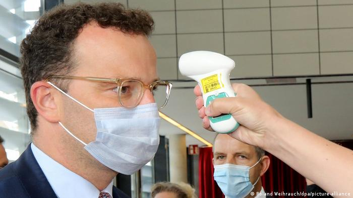 Bundesgesundheitsminister Jens Spahn bekommt bei einem Besuch der Universität Bochum die Temperatur gemessen (Foto: Roland Weihrauch/dpa/picture-alliance)