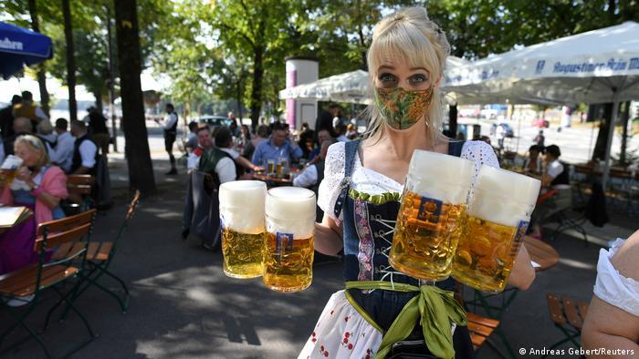 A Munich waitress carried beers (Andreas Gebert/Reuters)