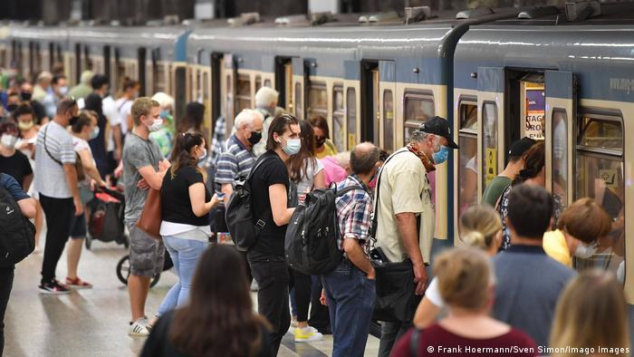People wearing face masks board a train in Munich