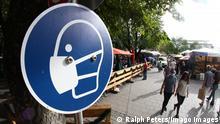 Schild mit Piktogramm Maskenpflicht am Biergarten Viktualienmarkt München
