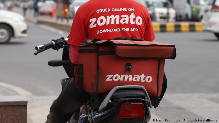 An employee of the Indian food delivery service Zomato waiting at a traffic signal in New Delhi