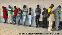 People access free Wi-Fi on their mobile phones at a public spot in Mutare, Zimbabwe