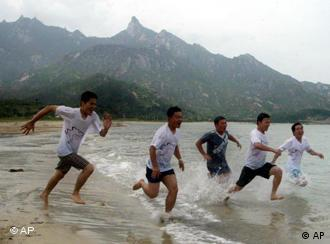 Tourists in happy times. South Koreans seen playing on Kumgangsan Beach in North Korea