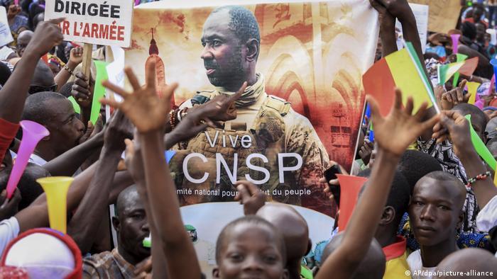 Malians cheer around a poster of junta leader Assimi Goita.