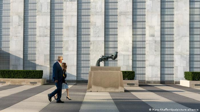 People walk by the renowned Knotted Gun statue outside the UN building in New York, September 21, 2020.