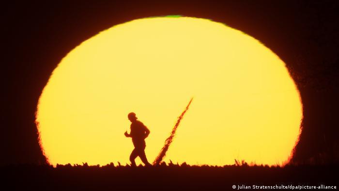 Homem caminha em frente a foto do Sol