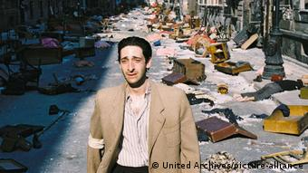 A still from the film ThePianist with Adrien Brody walking through a street strewn with trash