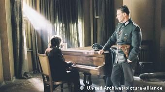 Filmstill Der Pianist, Roman Polanski Szpilman sits at a piano while a German officer stands next to him observing.