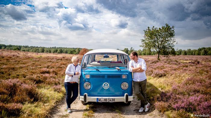 Antje und Arne Soetebier stehen mit VW-Auto in der Heide, Lüneburger Heide, Deutschland (HeideBulli)