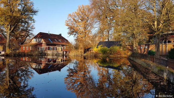Fachwerkhaus umsäumt von Wasser und Bäumen, Lüneburger Heide, Deutschland (Heideröster)