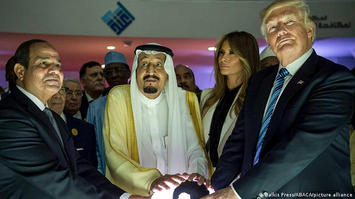 Egyptian, Saudi and US leaders stand holding an illuminated globe.