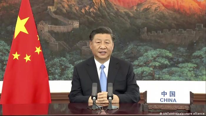 A picture of Chinese president XI Jinping sitting at a desk with a Chinese flag on his left side and a painting of the Chinese Wall behind him