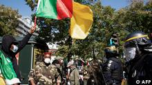 An opponent of current Cameroonian president waves a national flag in front of French riot policemen during a demonstration against Cameroon's President Paul Biya, near the embassy of Cameroon in Paris on September 22, 2020. - Paul Biya must leave: about fifty opponents of the Cameroonian president demonstrated September 22, 2020 in Paris in front of the embassy of Cameroon, and were pushed back by police after throwing projectiles. (Photo by - / AFP)