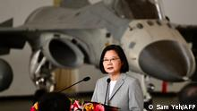 Taiwan's President Tsai Ing-wen (C) speaks in front of a domestically-produced F-CK-1 indigenous defence fighter jet (IDF) during her visit to Penghu Air Force Base on Magong island in the Penghu islands on September 22, 2020. (Photo by Sam Yeh / AFP)