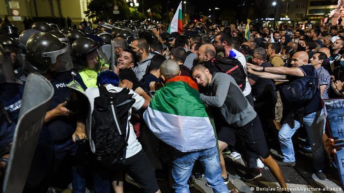 Полицейские с щитами и демонстранты с лагами Болгарии в Софии