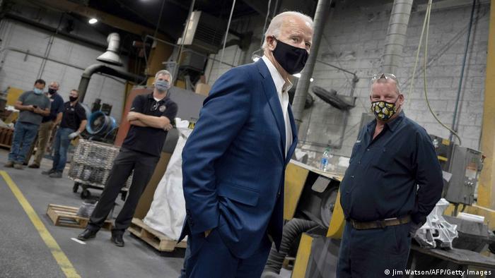 Joe Biden de máscara dentro de galpão de fábrica
