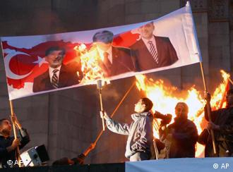 Armenians burn a poster with images of Turkish leaders during a rally in Yerevan, Armenia, Friday April 23, 2010, to commemorate the 95th anniversary of killings of Armenians by Ottoman Turks
