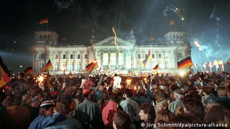 Multidão com bandeiras da Alemanha em frente ao Reichstag iluminado em Berlim.