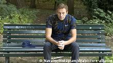 Alexei Navalny sitting on a bench after his release from hospital
