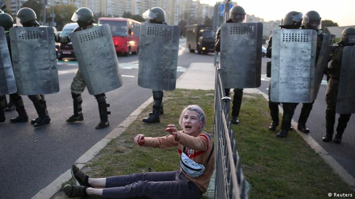 A woman reacts while sitting on the ground near Belarusian law enforcement officers, who disperse a crowd during a protest against the inauguration of President Alexander Lukashenko in Minsk, Belarus September 23, 2020.