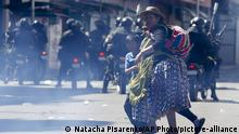 A woman crosses a street with a child crying aloud during clashes between supporters of former President Evo Morales and security forces, in La Paz, Bolivia, Thursday, Nov. 21, 2019. In an attempt to curb the social upheaval in Bolivia, interim President Jeanine Anez sent a bill to Congress to call for new elections amid an escalation of violence that has left 30 people dead. (AP Photo/Natacha Pisarenko) |