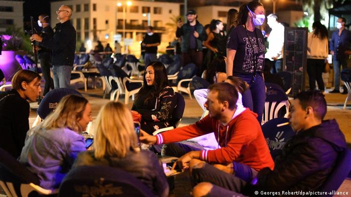 People sit outside a bar in Marseille, France