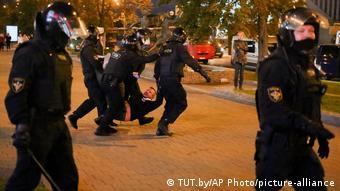 Милиционеры уносят с улицы демонстранта