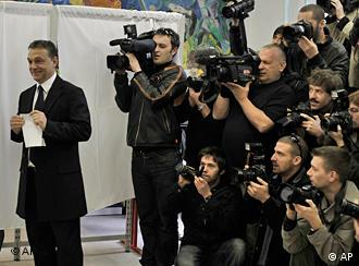 Orban stands in front of a bank of photographers