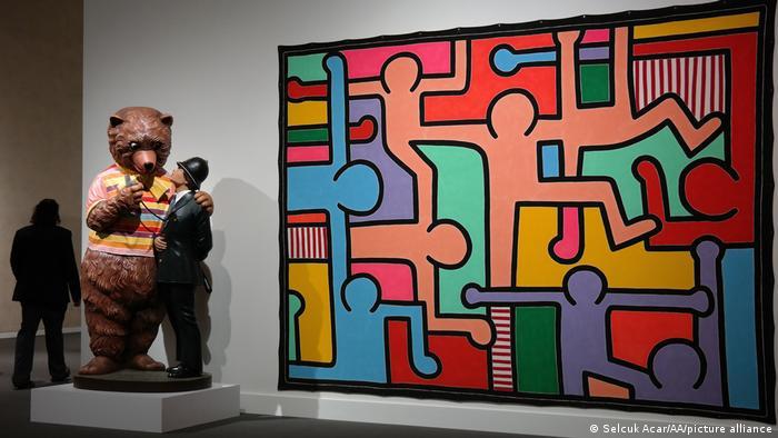 Eine Bärenskulptur von Jeff Koons steht neben einem Gemälde von Keith Haring, das bunt ausgemalte Figuren zeigt (Selcuk Acar/AA/picture alliance)