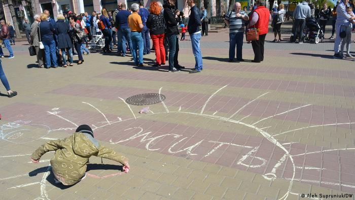 Ребенок пишет на площади в Бресте слово Жить