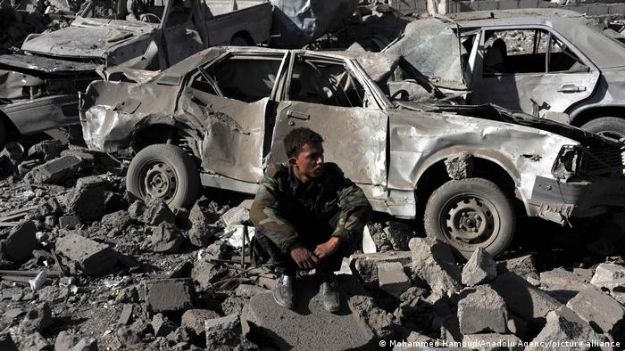 A man sits among the rubble in Yemen amid cars demolished by an airstrike
