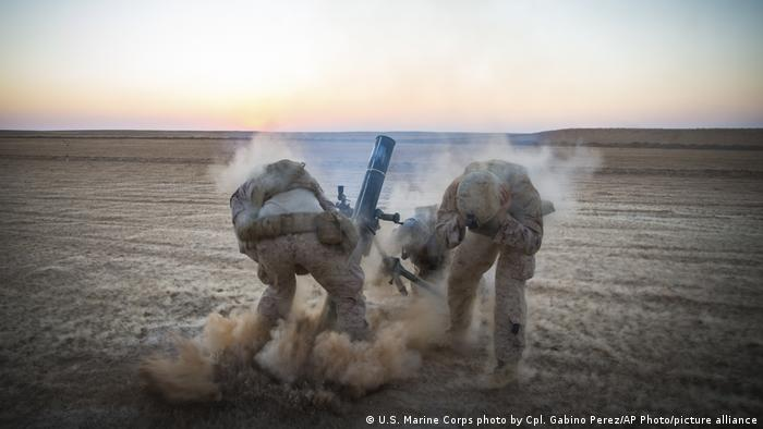US soldiers fire a mortar while ducking in Syria