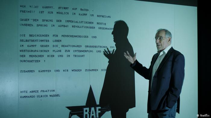 Man points to a large projection of a typed message with the RAF logo on the bottom (Netflix)