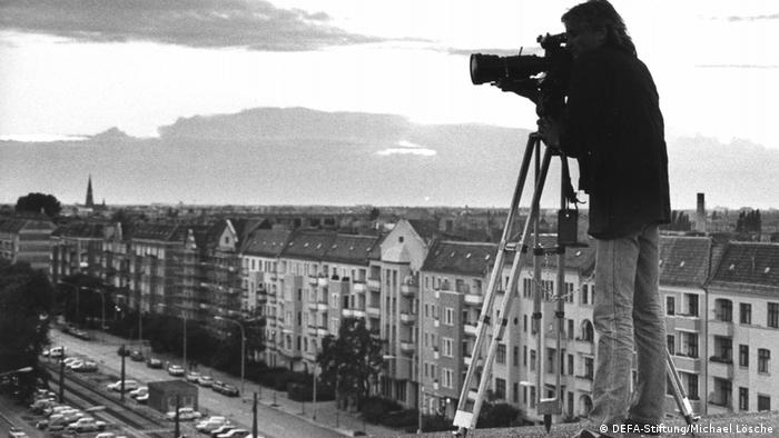 Film still Berlin — Prenzlauer Berg, a man with a camera and a ladder on a rooftop looking down at a city street with houses on one side, train tracks and parking slots on the other (DEFA-Stiftung/Michael Lösche)