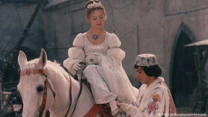 Film still Three Wishes for Cinderella, a young woman in a silver gown on a white horse, a young man in elaborate clothes and a cap holds her foot (DEFA-Stiftung/Jaromír Komárek)