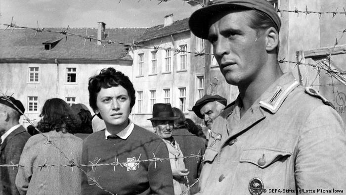 Film still Stars, a group of people behind barbed wire, a woman looks at a soldier who looks off into the distance (DEFA-Stiftung/Lotte Michailowa)