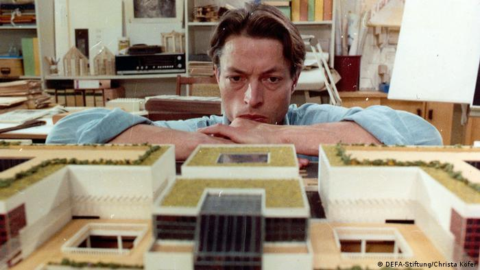 film still The Architects: A man crouches and looks at a architectural model of buildings