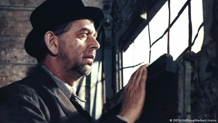 Film still Jacob the Liar, a man wearing a black hat looking out of a window (DEFA-Stiftung/Herbert Kroiss)