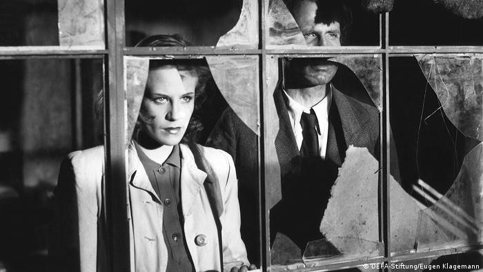 In a black and white film still, a woman and a man gaze through a broken window (DEFA-Stiftung/Eugen Klagemann)