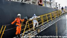 Members of Indonesia's National Search And Rescue Agency (BASARNAS) assist health quarantine officers wearing protective gears amid the COVID-19 coronavirus pandemic as they board the MV Loch Long during a medical evacuation at sea, off the Aceh coast on June 12, 2020. - The crewmember aboard the Panamas-registered LNG tanker, travelling from Brazil to Singapore was assisted off the ship due a medical-related issue. (Photo by CHAIDEER MAHYUDDIN / AFP) (Photo by CHAIDEER MAHYUDDIN/AFP via Getty Images)